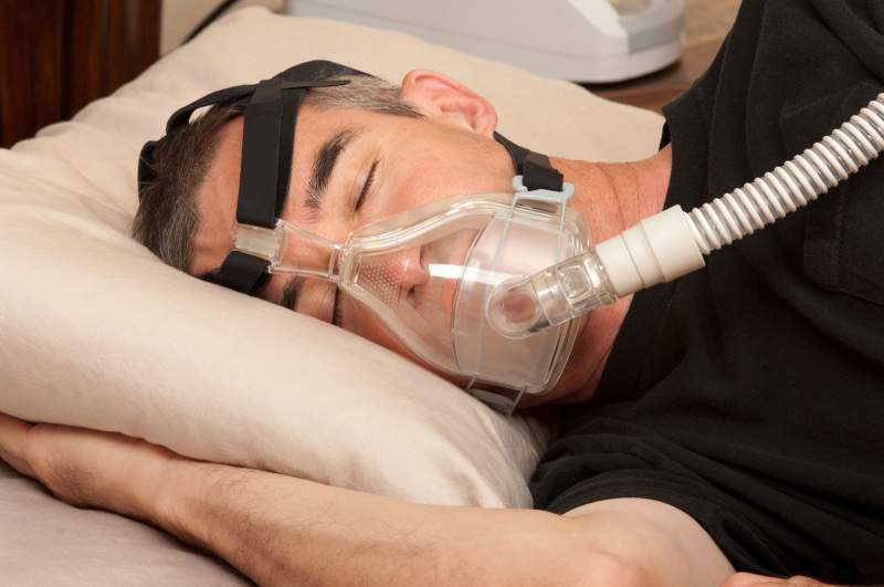Man sleeping with his CPAP machine attached
